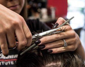 Women holding scissors cutting someone's hair
